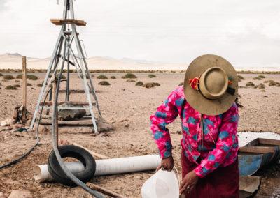 Mujer recolectando agua en un decierto en Santuario de Tres Pozos, Jujuy, Argentina
