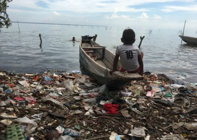 Un niño sentado en una canoa entre el agua y la basura en Pueblo Viejo Magdalena, Colombia