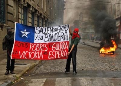 """Protestantes en Valparaíso, Chile, con una bandera chilena con las inscripciones: """"Saquen su grito y su bandera, somos pobres en guerra, la victoria nos espera."""""""
