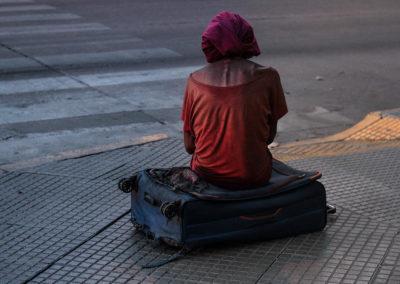 Mujer con ropas desgastadas, sentada sobre una maleta de ruedas también desgastada en la mitad de una vía peatonal. Córdoba, Argentina