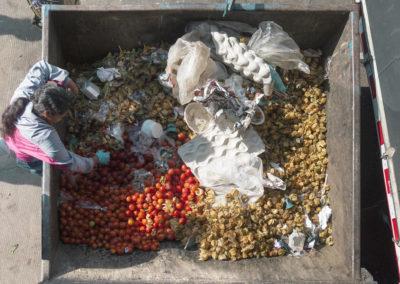 Mujer revisa la basura llena de frutas desechadas al final del día en Bogotá Colombia