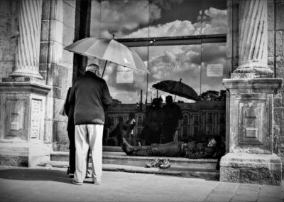Pareja de viejos en frente de un portal donde duerme un hombre afrodescendiente, la puerta es de vidrio y refleja la escena en Bogotá Colombia