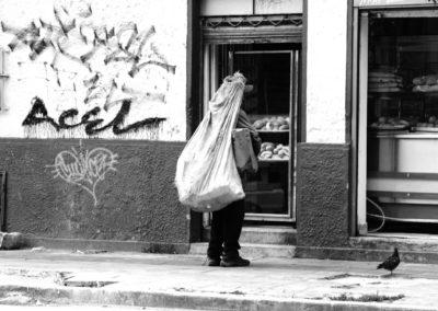 Reciclador, habitante de calle, mira hacia el interior de una panaderia en Bogotá Colombia
