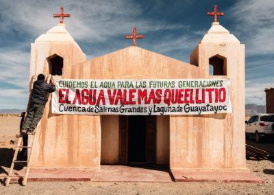 """Persona cuelga sobre la puerta de una iglesia un cartel que dice """"Cuidemos el agua para las futuras generaciones. El agua vale más que el litio. Cuenca de Salinas Grandes y Laguna de Guayatayoc"""" Aguas Blancas, Jujuy, Argentina"""