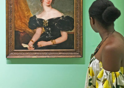 Mujer afrodescendiente con una blusa que deja ver sus hombros, observa un retrato al óleo de una mujer caucásica, con un vestido que deja ver sus hombros, y que le devuelve la mirada. En el Museo Nacional de Bellas Artes de La Habana