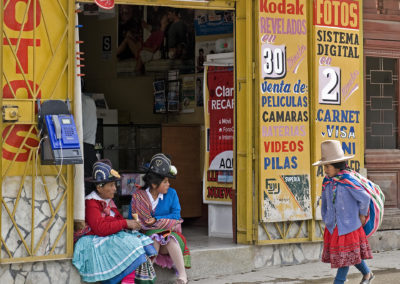 Mujeres indígenas sentadas a la entrada de un estudio fotográfico