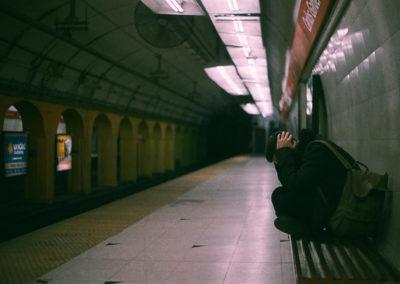 Persona esperando el metro subterraneo, sentada y cubriendose los oidos expresando desespero. En Buenos Aires, Argentina