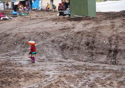 Mujer indigena camina por el barro al lado de tiendas y hogares en Vinicunca, Perú