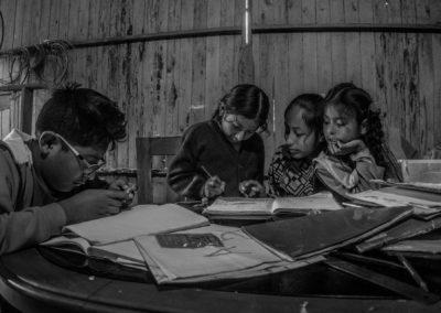 Tres niños estudian junto a su maestra con libros viejos y paredes desgastadas, en Los portales 7 de junio, Villa Maria del Triunfo, Lima, Perú