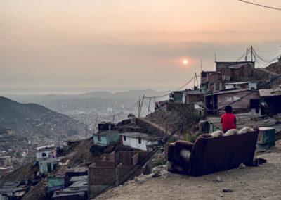 Paisaje desde Comas- Lima, Perú con un sillon a la interperie al borde de la montaña. Se ven casas a medio construir.