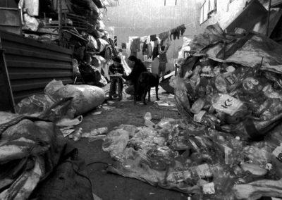 Mujer ayuda a su hijo con las tareas de la escuela rodeada de bolsas con material reciclable. San Martín de Porres, Lima, Perú
