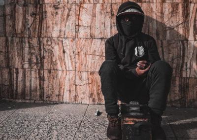 Un lustrador de zapatos con la cara cubierta, sentado esperando clientes en algúna calle de La Paz, Bolivia